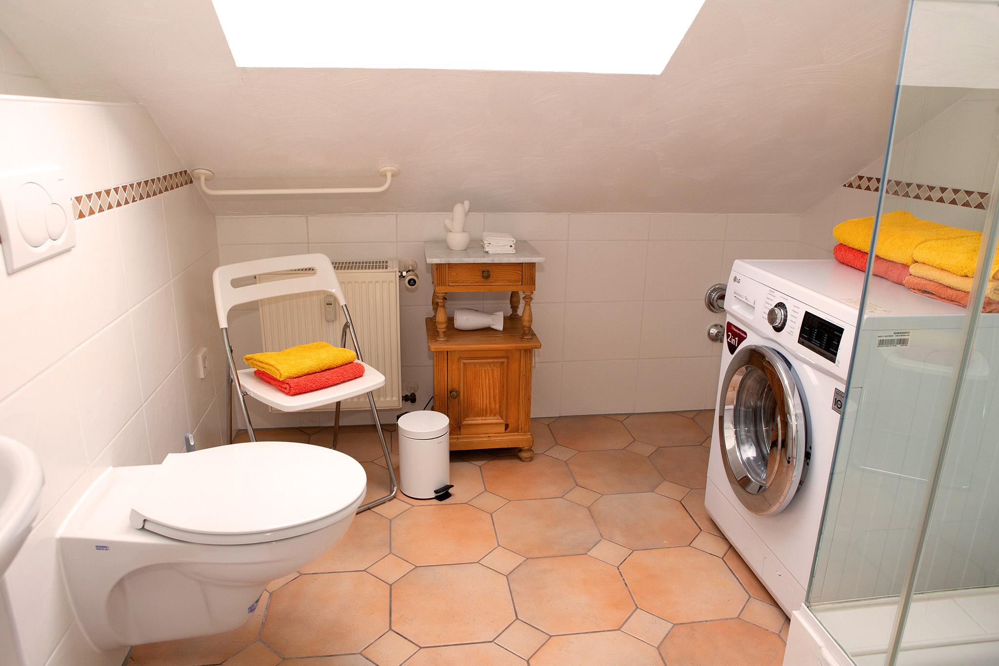 Das Badezimmer mit Waschbecken, Toilette, Dusche und Waschmaschine.
